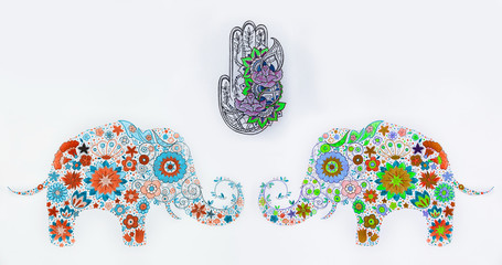 A set of sketches of hamsa and elephants in flowers on a white background.
