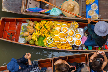Traveler enjoying and take a photo with smartphone on long trail boat at Damnoen Saduak floating market in Ratchaburi near Bangkok, Thailand