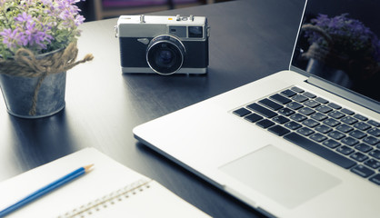 Creative working desk with notebook and vintage camera