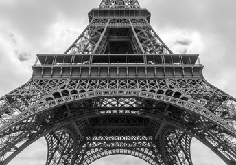 detail of Eiffel tower against clouds in black and white