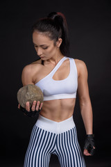 Portrait of fitness athletic young woman. Female model with muscular body in sports clothing holding heavy stone. Studio shot with copy space on black background.