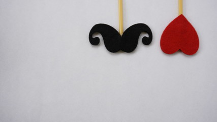 Top or flat lay view of Photo booth props red heart shape and a black mustache on a white background flat lay. Birthday parties and weddings.