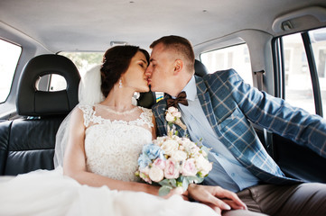 Gorgeous wedding couple kissing in a car.