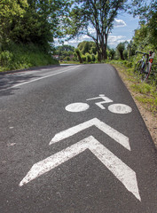white painted signpost for cyclists on the road