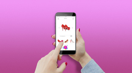 Girl buying shoes online on her phone on pink background