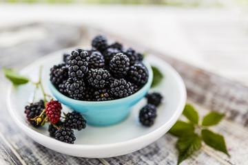 Fresh blackberries in bowl on wooden table in the garden.