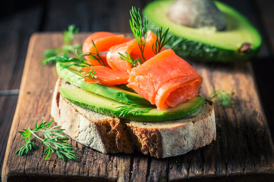 Closeup of sandwich with avocado, salmon and dill