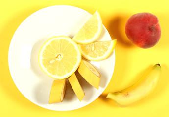 лимон свежий лежит на белой тарелке которая стоит на жёлтом фоне