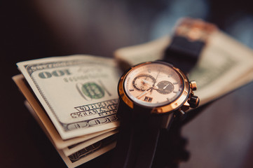 Yhe watches and 100 dollars closeup