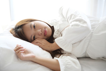 Asian young woman wake up with pillow in white room