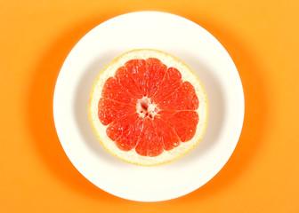 грейпфрут свежий лежит на белой тарелке которая стоит на оранжевом фоне