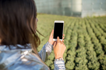 Woman holding a smart phone with blank screen on the modern hydroponic green house background