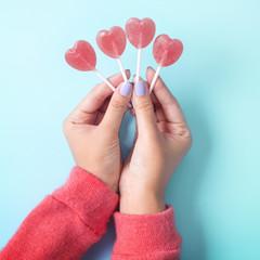 Holding Valentine's heart shape lollipop candy on sky blue background