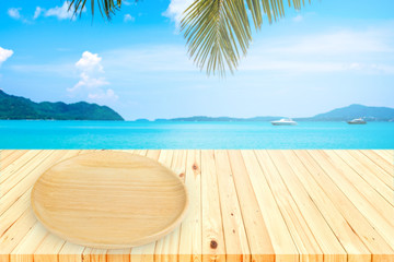 Wooden plate on table wooden board empty table in front of blurred sea background,can be used for display or montage your products. Mock up for display of product.