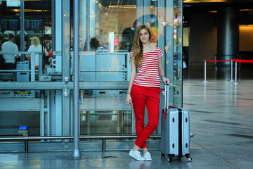Young beautiful girl standing close up with her silver suitcase in the airport