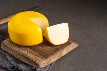 Round gouda cheese. Dark background.