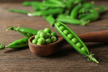 Wooden spoon with fresh green peas on table