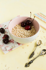 Oatmeal with berries on yellow background