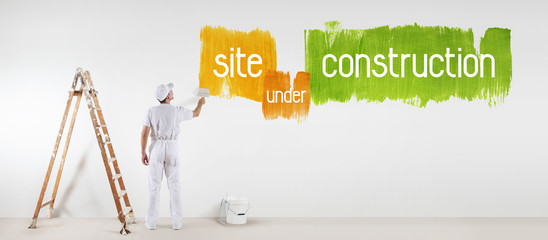 painter man with paint brush drawing under construction text isolated on the blank white wall