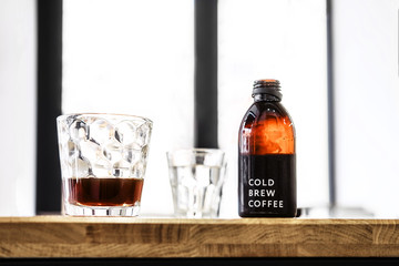 Filter cold brew coffee bottle and glass on a wooden table. Loft design