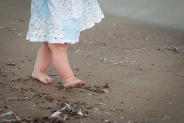 Cute toddler girl's legs on a beach