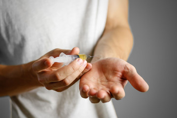 A young man injects himself in the hand syringe with a needle with the drug. Closeup. Isolated on a grey background