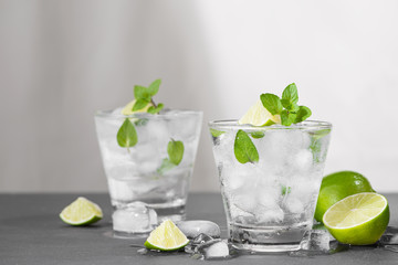 Mojito cocktail with lime and mint in glass on a grey stone background