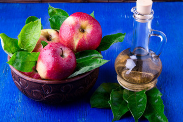 Apple cider vinegar in glass bottle on blue background. Red apples in brown bowl.