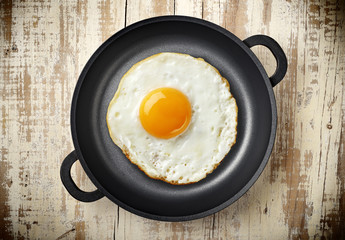 Tuinposter Gebakken Eieren fried egg on iron pan