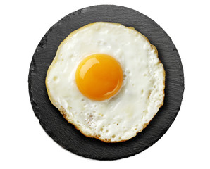 Poster Gebakken Eieren fried egg on round black slate