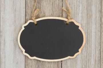 Hanging oval chalkboard on weathered wood wall