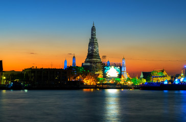 Wat Arun is a public facility, located on a river with evening light and light twilight in Thailand.