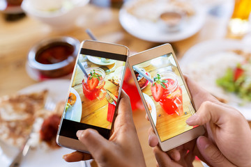 hands with drinks on smartphones at restaurant