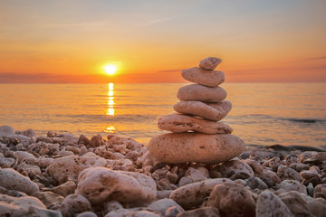 Pyramid of stones on the beach, beautiful sunset, sea landscape