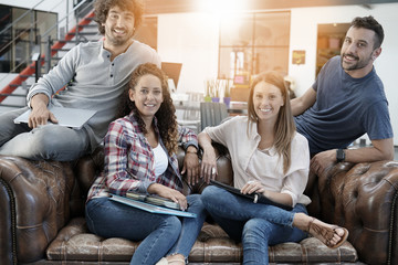 Group of trendy people sitting in office lounge couch