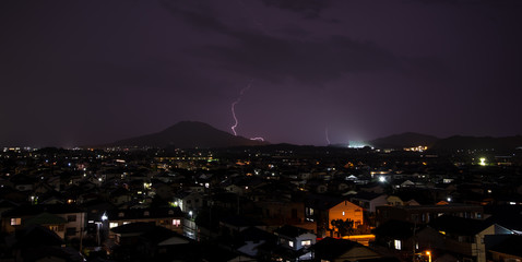 Lightning over City and mountain landscape panoramic