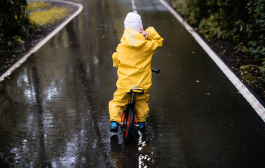Little girl ride on bike in a rainy day