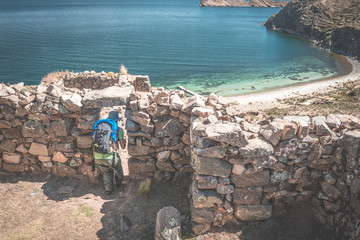Tourist exploring the ancient mysterious Inca labyrinth-like settlement, called Chinkana, on the Island of the Sun, Titicaca Lake, Bolivia. Travel adventures the Americas. Toned image.