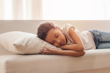 Adorable little african american girl sleeping on sofa at home