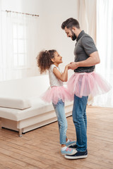 multicultural  father and daughter in pink tutu tulle skirts dancing together
