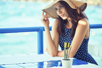 Young beautiful woman in a straw hat sitting in a tavern by the sea