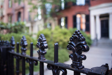 Beautiful wrought iron fence with carved posts in an old colonial neighborhood in New England.