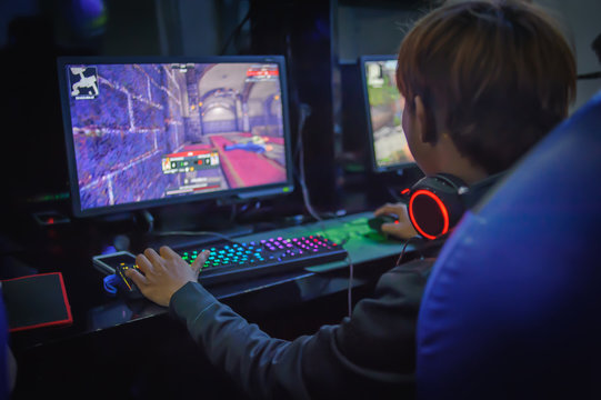 young man playing computer games in internet cafe