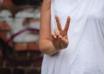Young woman's hands shows V sign. Gesture