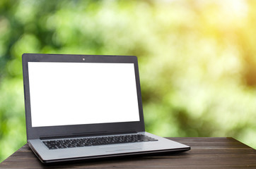 Laptop computer with white blank screen on wooden desk with nature green garden bokeh background with sunlight effect, working outside office, online social media technology, searching data concept