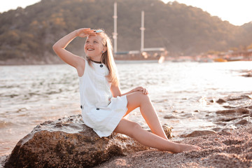 Romantic and happy blonde child cute girl sit on the stone near water at the beach in sunset magic light looks into distance. Stylish Kid has fun on sea coast. Summer vacation active lifestyle concept
