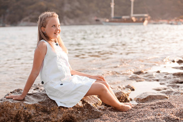 Romantic and happy blonde child cute girl sit on the stone near water at the beach in sunset magic light. Stylish Kid has fun on the sea coast. Summer vacation and active lifestyle concept