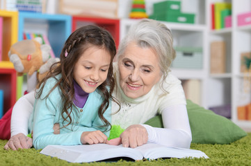 Grandmother reading book with her granddaughter