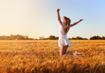 Beautiful young girl in white dress jumping in golden wheat