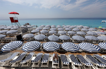 A tourist enjoys the sun on a beach covered with umbrellas on the Promenade Des Anglais during a sunny summer day in Nice